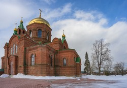 Ancient church in the village of Mezenskoe (Middle Ural, Russia) on a sunny spring day. Embossed brick walls, arched windows. Several towers crowned with golden domes. Blue-white sky and bare trees