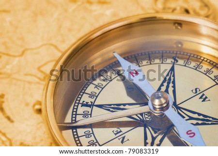 Ancient compass on the grunge old map