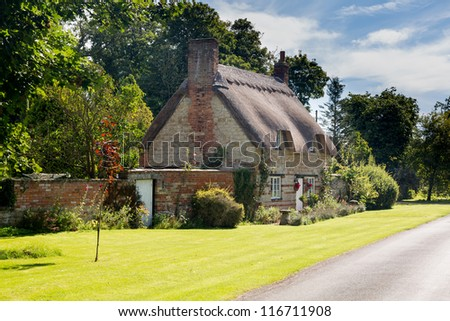 Ancient cotswold stone house and flower garden in Cotswold village of Honington