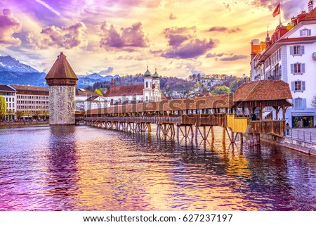 Ancient covered wooden Chapel Bridge Kapellbrucke and Water Tower Wasserturm on the background of the snow covered Pilatus Mountain in the historic center of Lucerne at sunset, Switzerland