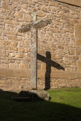 Ancient cross on stone wall. Stone old crucifix with shadow on monastery backyard. Christianity symbols. Medieval cemetery. Cross and shadow. Catholic religion. Spiritual background.