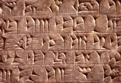 Ancient cuneiform from Babylon in Mesopotamia. Assyrian and Sumerian writing carved on clay or stone. Remains of the culture of ancient civilization in the Middle East. Old cuneiform script close-up.