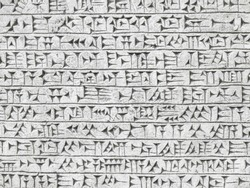 Ancient cuneiform from Babylon in Mesopotamia. Assyrian and Sumerian writing carved on clay or stone.  High resolution. Old cuneiform script close-up.