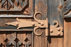 Ancient decorative door hinge on antique wooden ornamental door of vintage rural house in Suzdal town, Russia. Russian traditional national folk style in architecture. Architectural detail of building