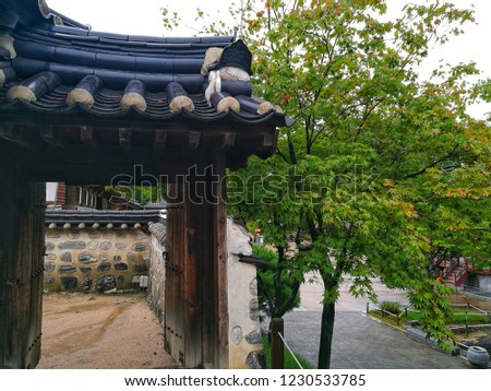 Ancient door facade of Korea's house that made from wood and black roof tiles on top. It is opening with a view of traditional fence inside and constructed near green tree and path way of that area. #1230533785
