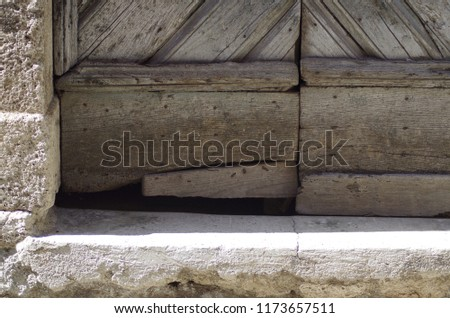 Ancient door in damaged solid wood, with access step to the house in travertine, in a medieval village. #1173657511