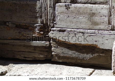 Ancient door in solid wood damaged by termites, with access step to the house in travertine, in a medieval village. #1173678709