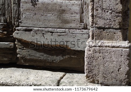 Ancient door in solid wood damaged by termites, with access step to the house in travertine, in a medieval village. #1173679642