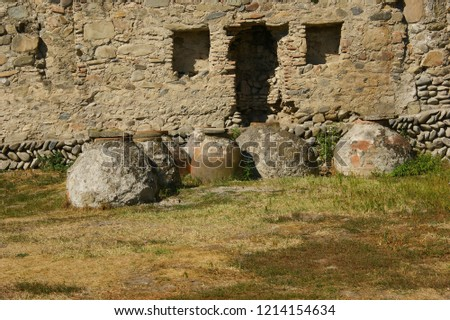ancient earthen vessels against the background of the fortress wall