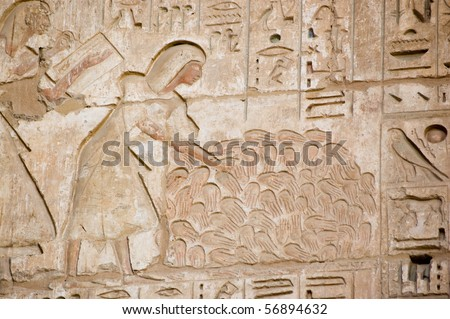 Ancient Egyptian carving showing scribes counting the hands of women killed in battle by the forces of Ramses II.  Temple of Medinet Habu on the West Bank of the Nile at Luxor, Egypt.