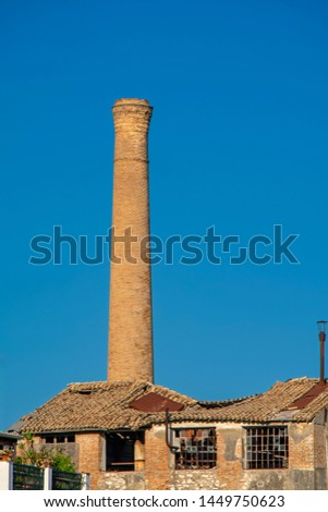 Ancient factory brick pipe and old brick buildings with tile roof against the blue sky. Urban industrial view. Contrast minimalistic scene with vintage building #1449750623
