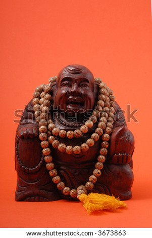 Ancient figure of budha monk made of red wood and surrounded by indian nacklace mala - stock photo