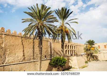 Ancient fortress and tunisian palms, castle wall made of yellow brick or stone are standing in Sousse city on the shores of the Mediterranean Sea are a tourist attraction in the tourist area #1070768039