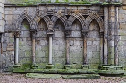 Ancient gothic stone wall with arches and columns, ruins Holyrood Palace in Edinburgh, Scotland, UK