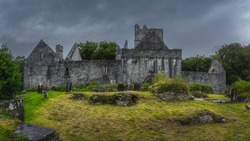 Ancient graveyard and tombs in front of ruins of 15th century Muckross Abbey with dramatic storm sky, Killarney National Park, Kerry, Ireland
