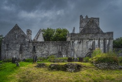 Ancient graveyard in front of ruins of 15th century Muckross Abbey with dramatic storm sky, Killarney National Park, Kerry, Ireland