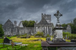 Ancient graveyard with Celtic cross tombstone and ruins of 15th century Muckross Abbey, Killarney National Park, Kerry, Ireland