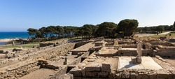 Ancient greek and roman ruins by the Mediterranean sea, famous archaeological site in Empúries, statue of Asclepius god of medicine in ancient Greek mythology, Costa Brava, Spain. Panorama picture