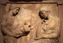 Ancient Greek bas-relief on grave stele, marble sculpture of women and child, funeral scene carved in stone in cemetery. Traditional monument of classical Greece culture. Concept of death and sadness