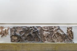 Ancient greek parts of marble plaque with battle scene in museum of Delphi, Greece. Greek basrelief carved on surface, exhibits on white wall background