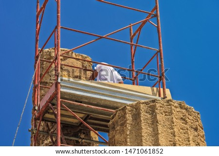 Ancient Greek Roman temple restoration scaffoldings. Unidentified worker on metal construction to support repair & preservation at Temple of Juno - Hera in Agrigento Sicily Italy archaeological site. #1471061852