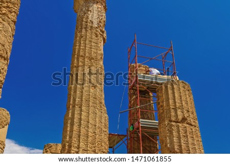Ancient Greek Roman temple restoration scaffoldings. Unidentified worker on metal construction to support repair & preservation at Temple of Juno - Hera in Agrigento Sicily Italy archaeological site. #1471061855