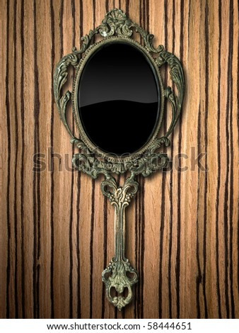 ancient hand mirror on zebrano Wood background