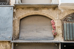Ancient headstone in a niche wall with old red plastic flowers on one side.