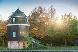 ancient historic water crane building with stone foundation and wooden top costruction at waterway of river saar in saarbrucken saarland germany during sunset at beautiful autumn day colorful tree