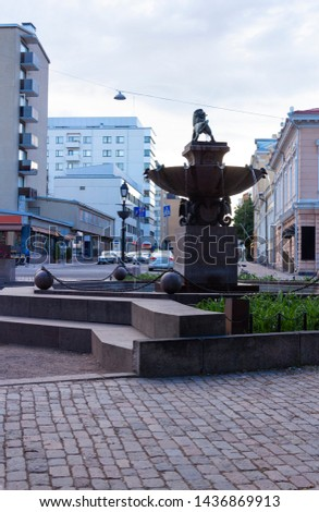 Ancient historical city fountain with a lion sculpture near historic buildings on Linnankatu street in the center of Turku in Finland on a summer day.