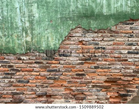 Ancient house wall Green plaster surfaces with stains caused by the expiration of the color. The putty surface makes the construction material visible. Orange antique bricks, black and white bricks