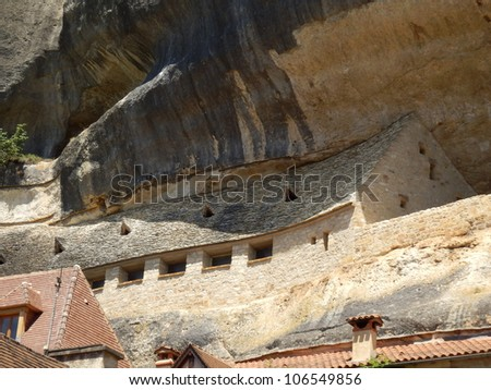 Ancient house with a stone tiled roof built into a cliff face in the town of Les Eyzies, Dordogne, France - stock photo