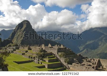 Ancient Inca lost city Machu Picchu landscape with clouds.