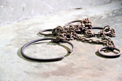 Ancient iron shackles, used to chain slaves, lie on the cold concrete of a dungeon at the old slave-trading port of Stone Town, Zanzibar.