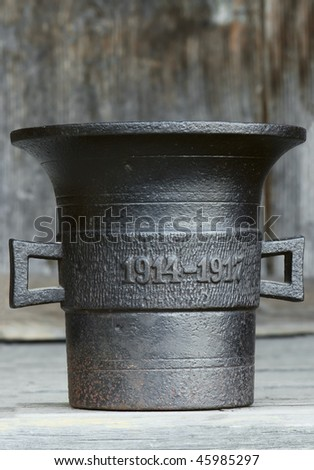 Ancient kitchen and medical utensil. Old metal mortar on wooden background, aged 1914-1917