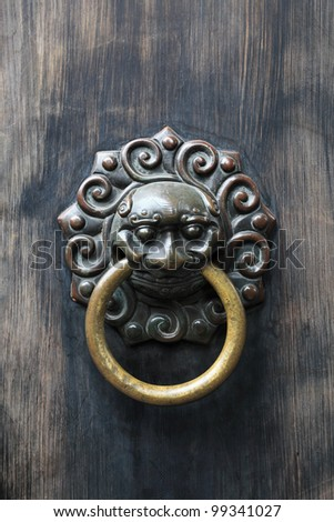 ancient knocker on traditional door - stock photo