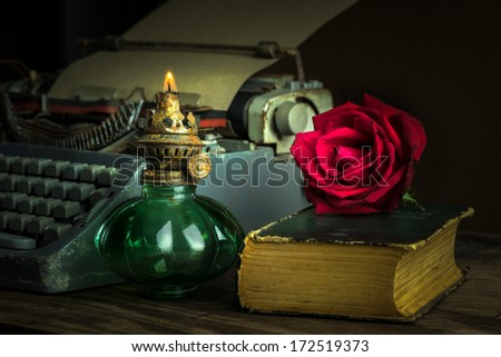 Ancient lantern on wooden table with red rose bud on old book and typewriter