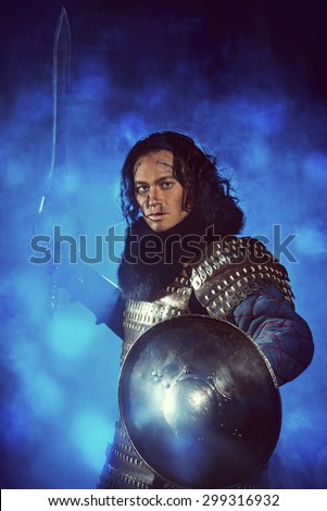 Ancient male warrior in armor holding sword. Historical character. Fantasy.