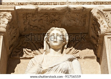 Ancient marble statue of a woman looks out under intricate archway copy space (statue is Sophia, Goddess of Wisdom, at the Celcus Library at Ephesus, Turkey)