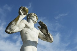 Ancient marble statue of muscular athlete shot put thrower throwing a shot against bright blue sky