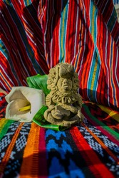 Ancient Mayan figure sitting in the form of a woman with decoration and a basket in her hands and flower back with typical background