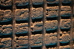 Ancient Mayan glyphs/pictograms carved in a stone slab.