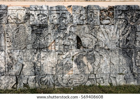 Ancient Mayan mural at the Great Ball Court in Chichen Itza depicting a player holding a knife  and a severed head in another. Opposite him a headless body with the snakes streaming out of the neck. #569408608