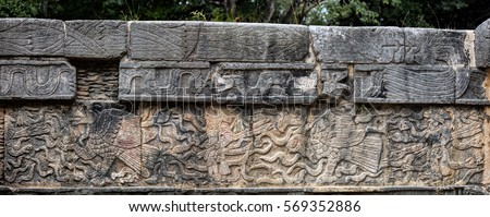 Ancient Mayan mural depicting an eagle grasping a human heart and a warrior holding a human head on the Platform of the Skulls, a.k.a. Tzompantli in Chichen Itza, Yucatan, Mexico #569352886