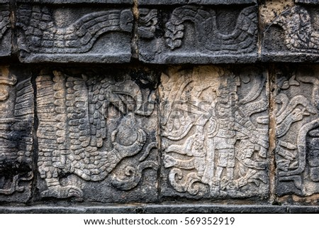 Ancient Mayan mural depicting an eagle grasping a human heart and a warrior holding a human head on the Platform of the Skulls, a.k.a. Tzompantli in Chichen Itza, Yucatan, Mexico #569352919