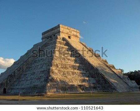 Ancient Mayan pyramid Chichen Itza in Mexico, Riviera Maya with blue skies above and grass field below, trees in background