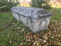 Ancient medieval gravestone of limestone in the Russian monastery cemetery. Skull and bones at the end of the crypt.