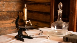 Ancient microscope in an old authentic laboratory. Rural old medical laboratory.