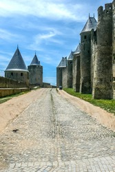 Ancient narrow streets in the old town of Carcassonne with stone walls
