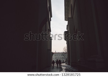 Ancient narrow Vilnius street with dark people silhoettes #1328181725